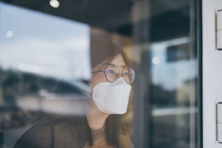 woman looking through window with mask